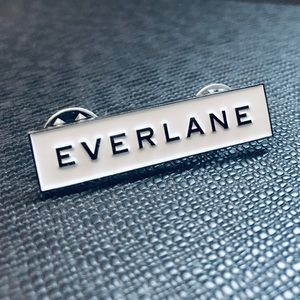 Small white and silver Everlane enamel pin